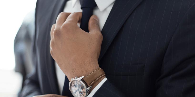 person adjusting tie on suit